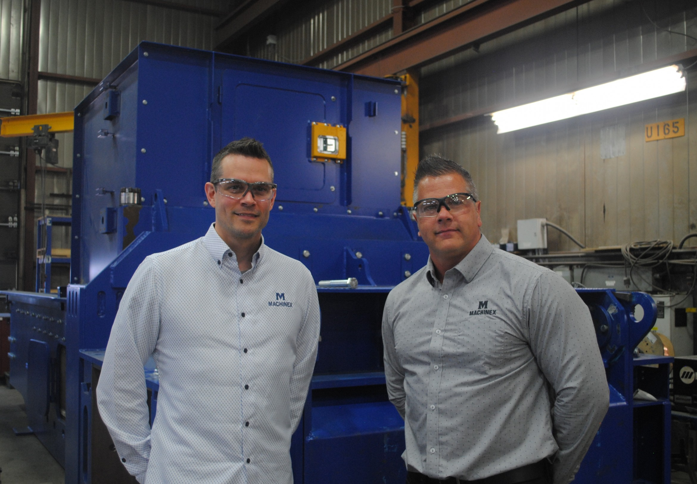 Two Machinex employees in front of Machinex equipment