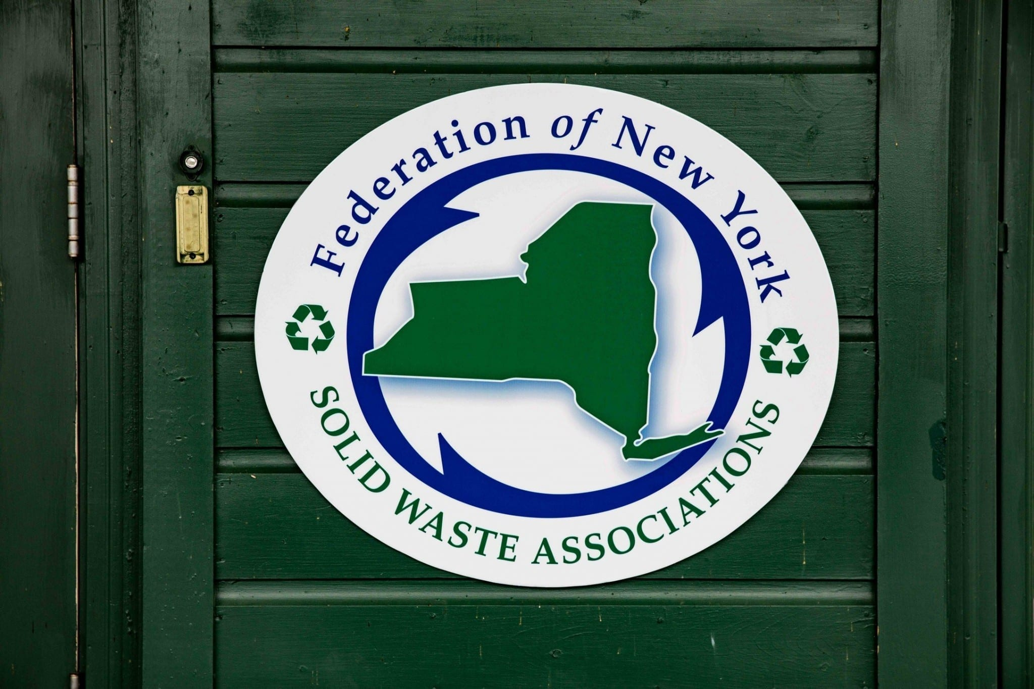 NY Federation solid waste association logo on a wood door